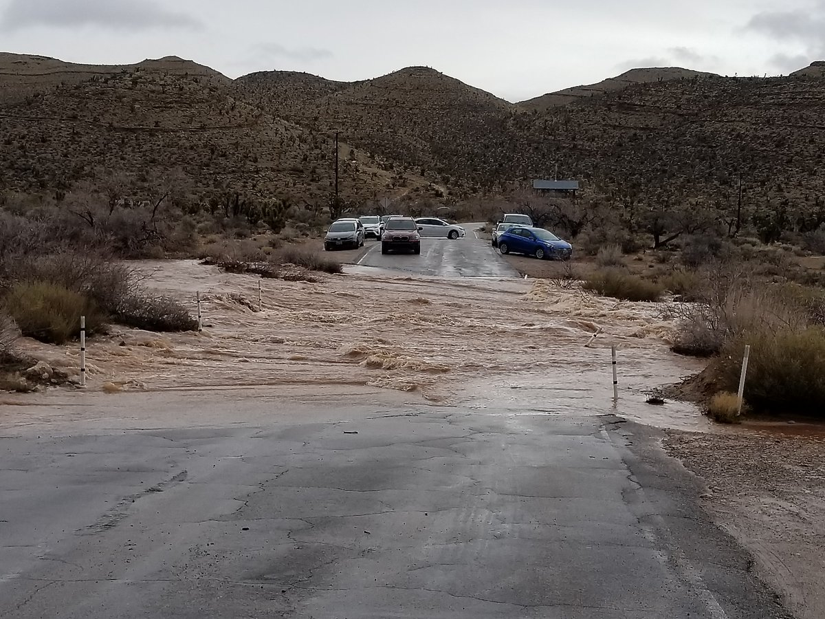 Floodwater rushes across a road in Bonnie Springs, Nevada, while cars turn around.